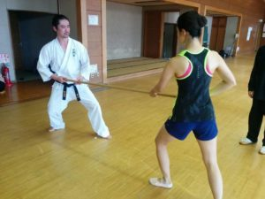 Miyakawa hanshi demonstrating center of mass transmission with seminar participant using a rokushakubo